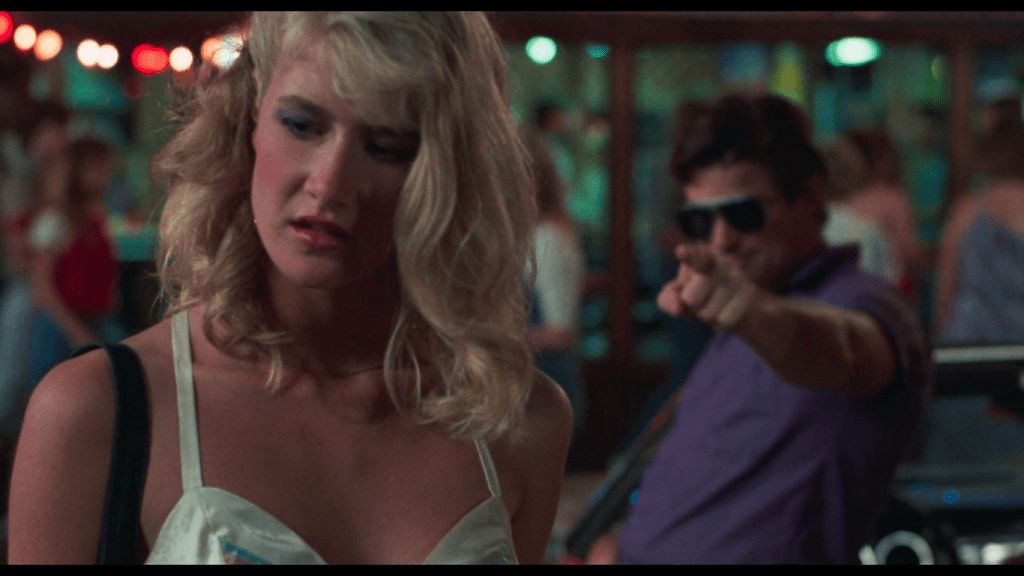 a man in sunglasses points menacingly at Connie, a blonde teenager played by Laura Dern