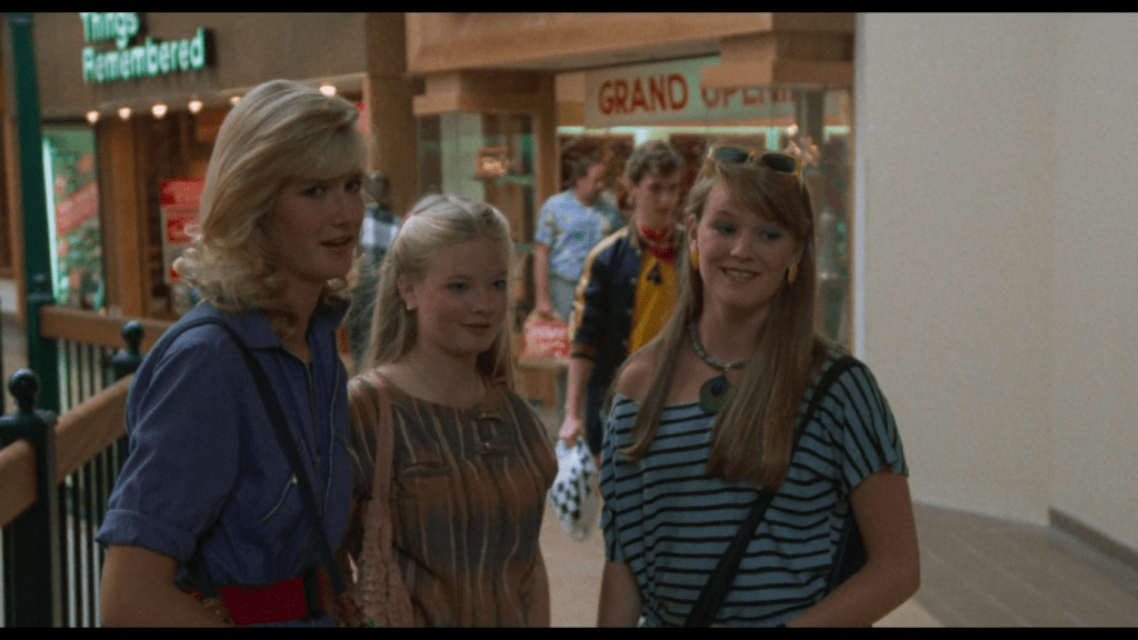 Three blond teenagers stand in the middle of a walkway in the mall, looking offscreen