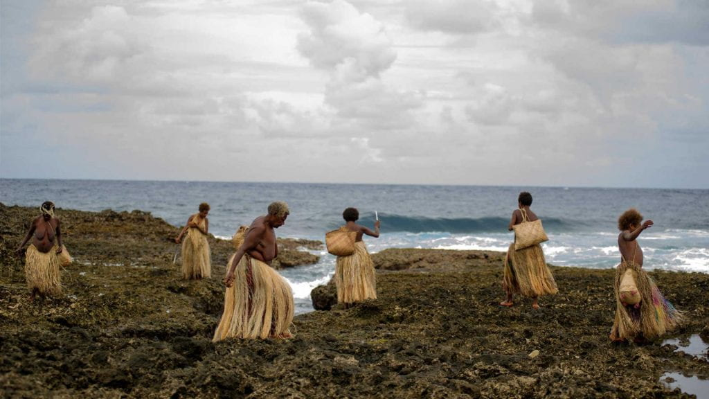 Women on the shore collecting shells for a bridal necklace in TANNA