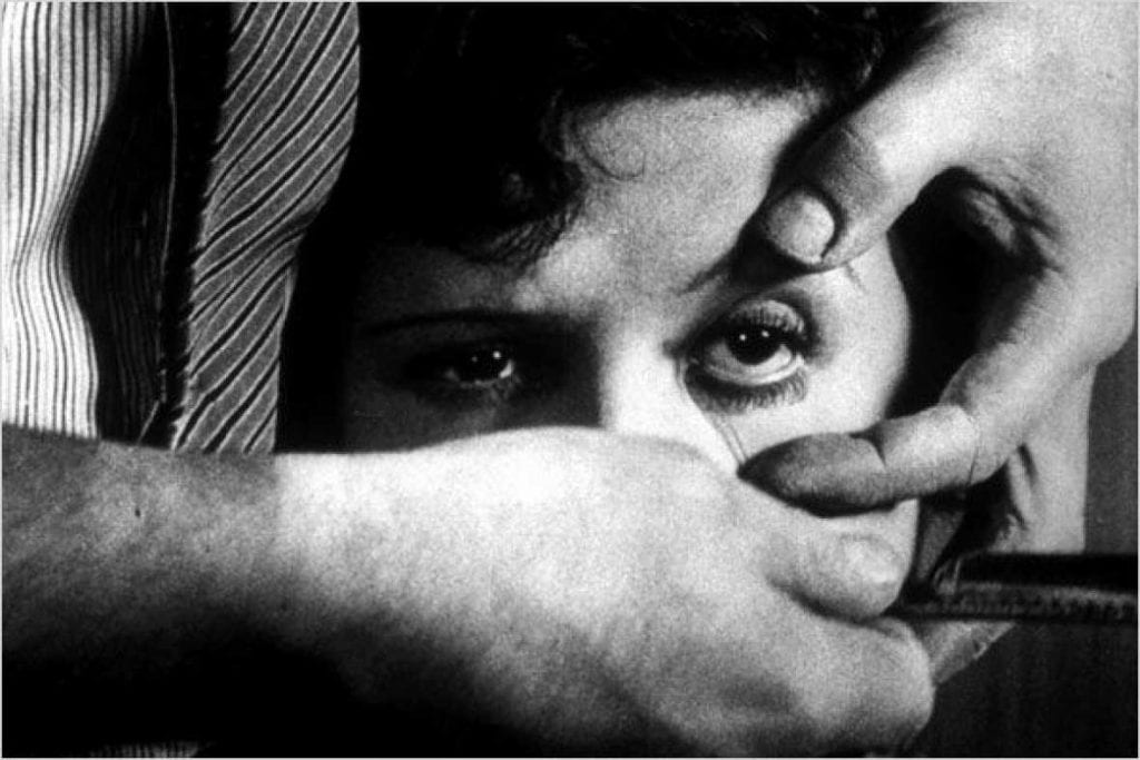 a man holds a woman's eye open with his fingers and holds a razor under her eye