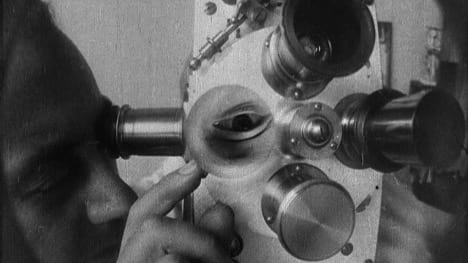 a man looks into an old film projector. We see his eye, upside-down, in one of the lenses.