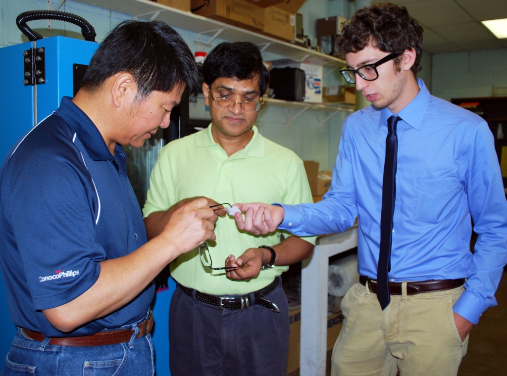 Dr. Chien Pan, Project Manager from ConocoPhillips, Dr. Mrinal Saha, Associate Professor at AME, and Elias Marsee, AME undergraduate researcher, observe tested insulation material.