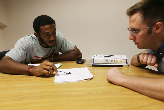 Cornerback Jordan Thomas reviews a chemistry assignment with his tutor Wednesday evening. Photo by Tony Ragle/The OU Daily