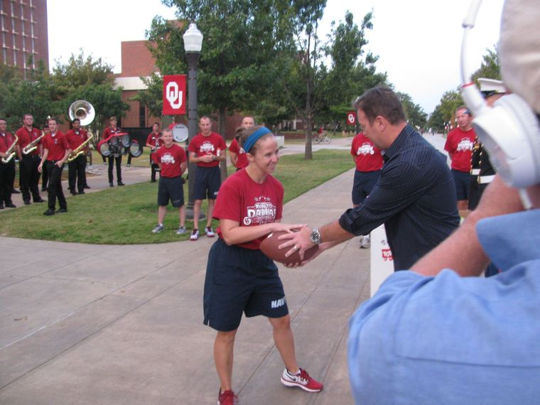 Ashley Carpenter, Aerospace Engineering Senior and ROTC Naval student, accepts the Cotton Bowl football from OU Football Coach Bob Stoops to begin the trek to Dallas.