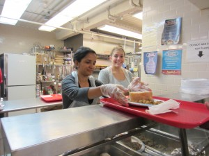 Two volunteers from Pace University serve dinner to hungry New Yorkers at NY Common Pantry.