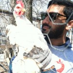 One of our former student staff members, Hasin, holding a chicken during Hands On New York Day.