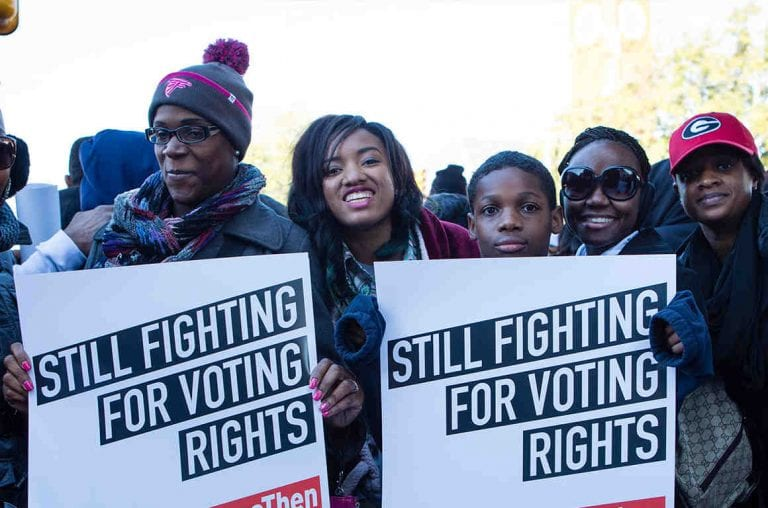 "People holding posters that state ""STILL FIGHTING FOR VOTING RIGHTS"""