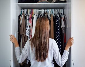 A woman standing at the entrance of her closet.