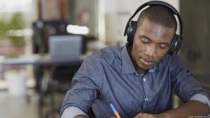 A student wearing headphones and doing work.