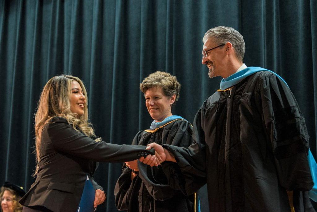 SJSU Lurie College Associate Dean Marcos Pizarro congratulates a scholar.