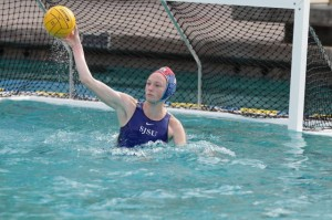 Female water polo player in the water hitting ball.