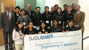 student, faculty and alumni group photo with banner