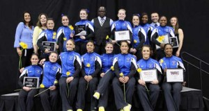 Gymnastics team poses in uniform holding their awards with their coach. (black background.)