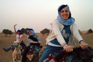 Three female SJSU students riding camels in desert.