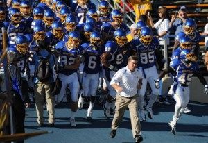 SJSU football team running out on to field behind coach. The team is suited up in their uniforms.