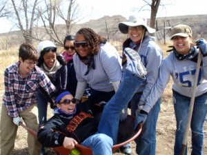 Students and staff pose with a wheelbarrow and tools in the Dine' (Navajo) Nation. Photo by Angela Gonzaga.