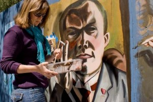 Female student (Kelsey) with paint brush working on mural of Max Beckmann.