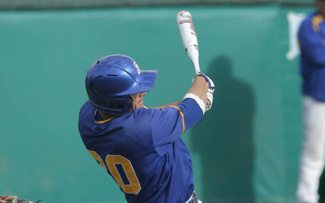 Michael DiRocco seconds after swining the bat. He is wearing a blue helmet and a blue jersey with a white baseball bat.