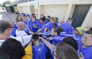 The swim team gathers for a group huddle.