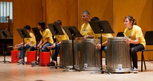 "Recent SJSU graduate Joseph Reichert, center, and his percussion pupils perform the song ""Funky Buckets"" with metal garbage cans, plastic buckets and drumsticks at the Music Building Concert Hall on June 24. Photo by James W. Murray."
