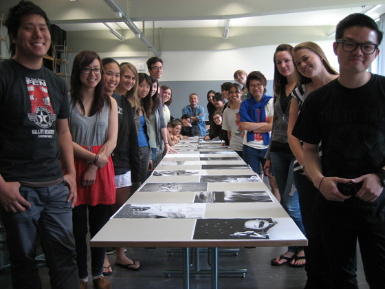 Graphic design students line up on both sides of a long table and pose for photo.