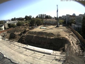Aerial view of construction at the west side of the Student Union, including a tall pile driver and a big hole in the ground. Photo courtesy of MoreCampusLife.com