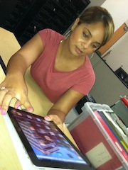 Student leans ipad on her desk to demonstrate how easy it is to use.