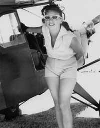 Black and white photo of Amelia Reid with an airplane.