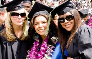 Three ethnically diverse female grads at commencement.
