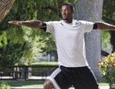 James Jones in yoga pose outdoors on campus.