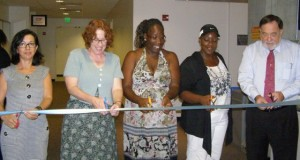 Students, a professor and the provost cut the ribbon on new offices.