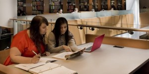 Two students working together on laptops at King Library