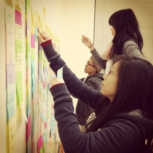 San Jose State students put up post-it notes on a bulletin board in a classroom.