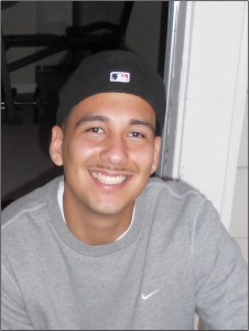Daneil Guzman is standing in front of a doorframe, smiling to the camera wearing a baseball cap and sweatshirt