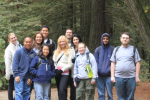 Students gather in front of sequoia trees to pose for a picture at the Nicene Marks State Park. They are wearing jackets and have backpacks on ready to hike.