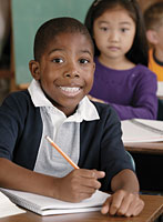 male student holding pencil in classroom