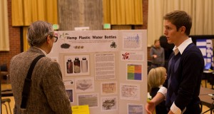 Junior JD Leadam stands to the left of his project poster board for Hemp Plastic Water Bottles presented his idea to a passerby. Poster board includes a picture of the design and an explanation of his project