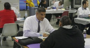 Javier de la Torre assists a client at the McKinley Neighborhood Center Speed Screening