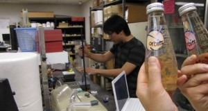 student in lab in background, soft drink bottles with pearls floating inside in foreground