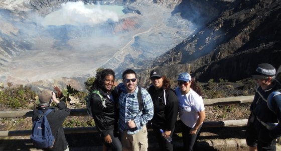 4 students standing before steaming volcano