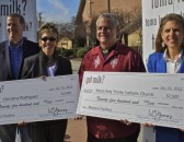 Four people with big checks from the milk board.