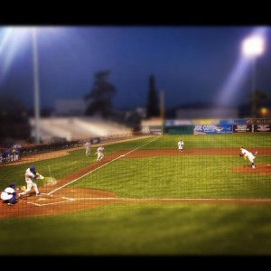 Photo taken from the stands looking down on the SJSU baseball team at night.
