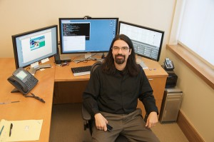 Dr. Michael Stephens at his desk, with three monitors behind him.