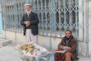 two men in traditional clothing with a wheelbarrow full of bananas