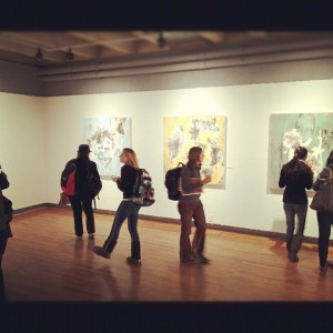 ive students in an art gallery viewing large paintings.