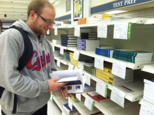 A student stands in front of books to rent in the bookstore