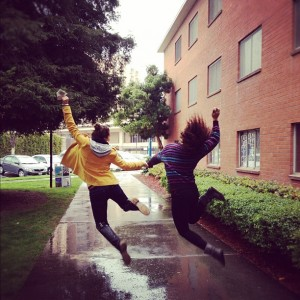 two students dancing in the rain outside the bricks