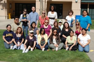 SJSU Faculty, Staff, and Student Pose for a picture on the grass in The Village Quad