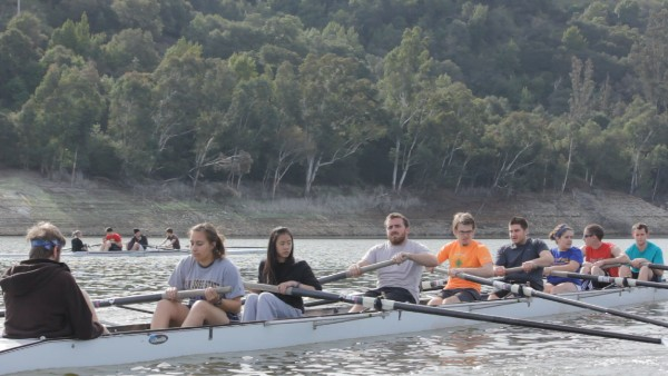 six students using oars to row a boat