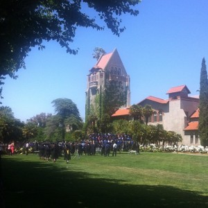 Tower hall in the background with over 100 students in cap and gown.